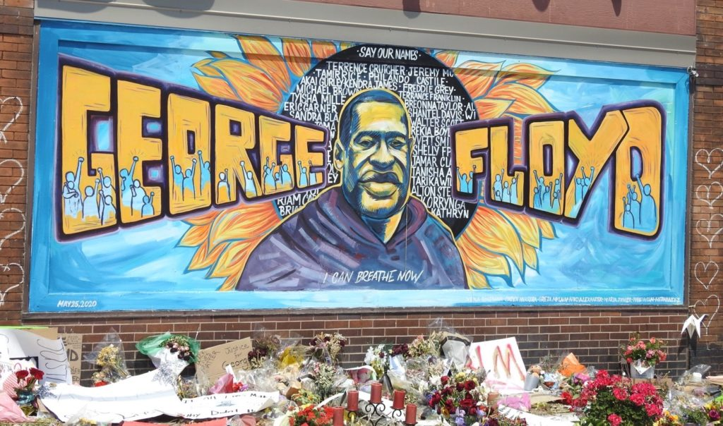 The mural of George Lloyd at Cup Foods with the memorial flowers under it.